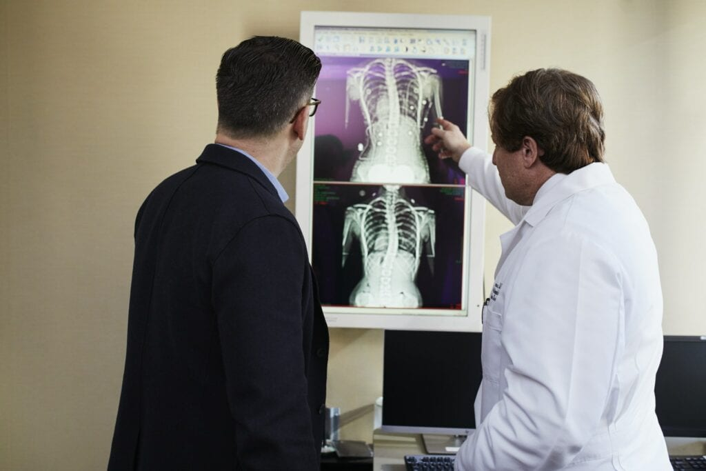 two doctor's looking at an x ray