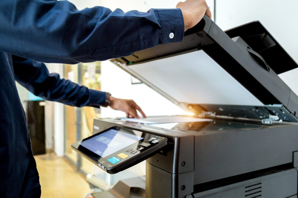 man scanning paper document on a copier