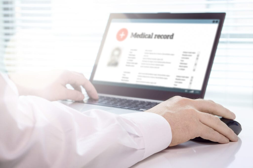 doctor using laptop with electronic medical records on screen