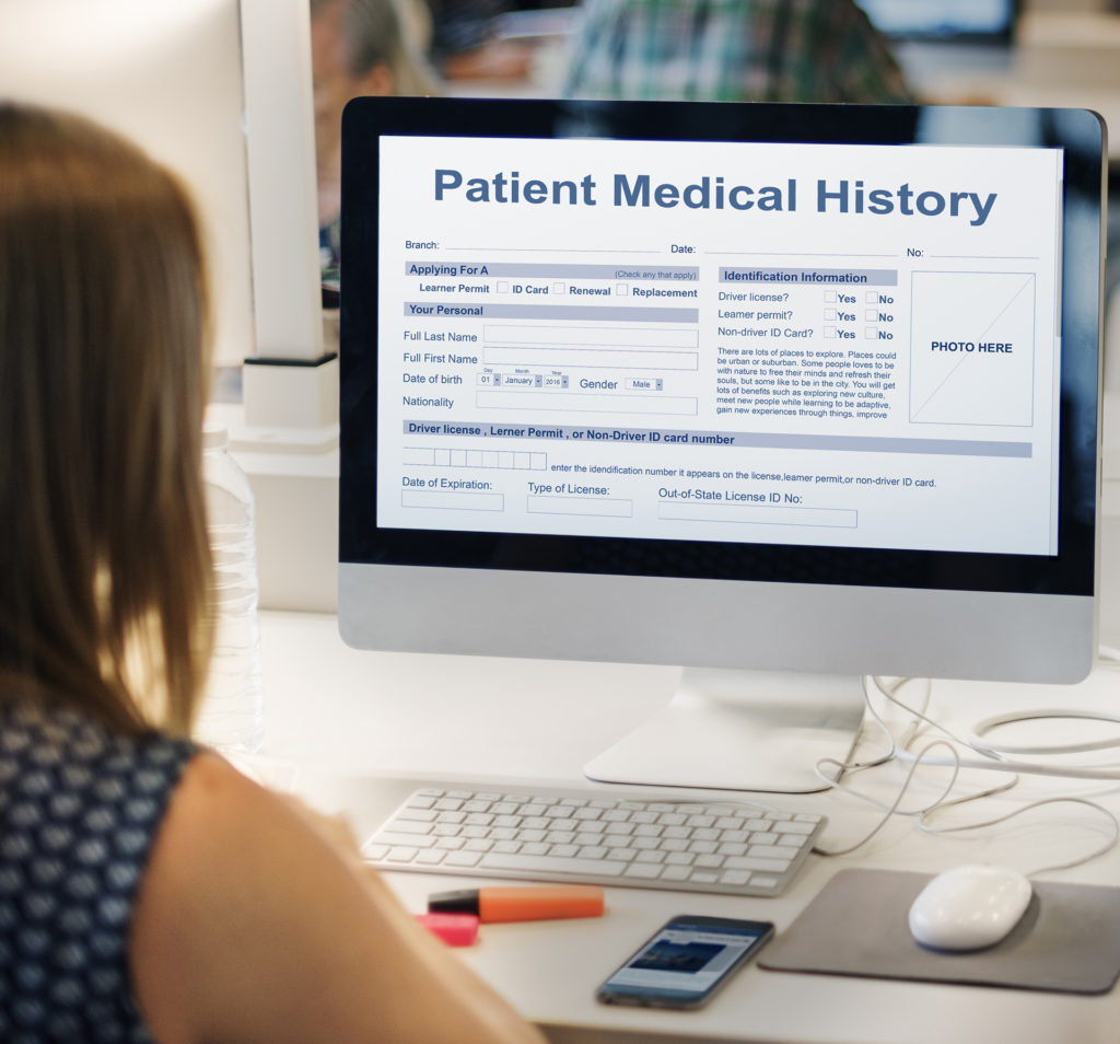 woman looking at patient medical history form on computer